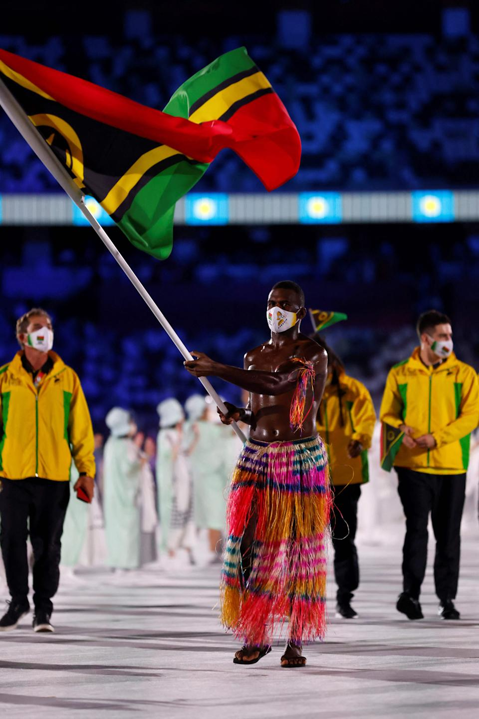 <p>Vanautu's flag bearer Riilio Rii parades during the opening ceremony of the Tokyo 2020 Olympic Games, at the Olympic Stadium, in Tokyo, on July 23, 2021. (Photo by Odd ANDERSEN / AFP) (Photo by ODD ANDERSEN/AFP via Getty Images)</p>