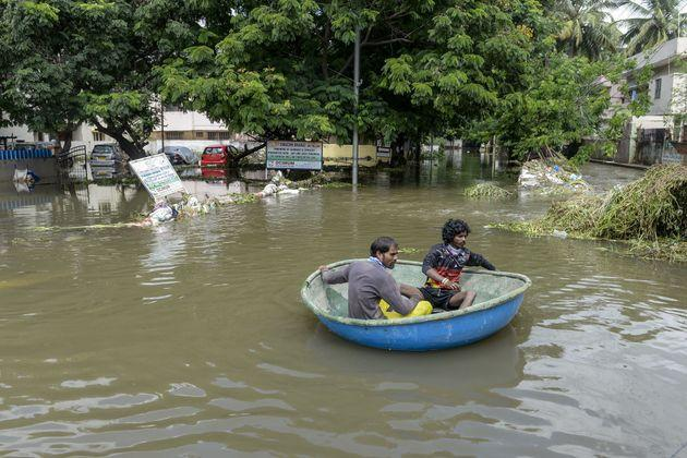 Cantonment Board workers use a boat to evacuate residents on a flooded street following heavy rains in Hyderabad on October 15, 2020.