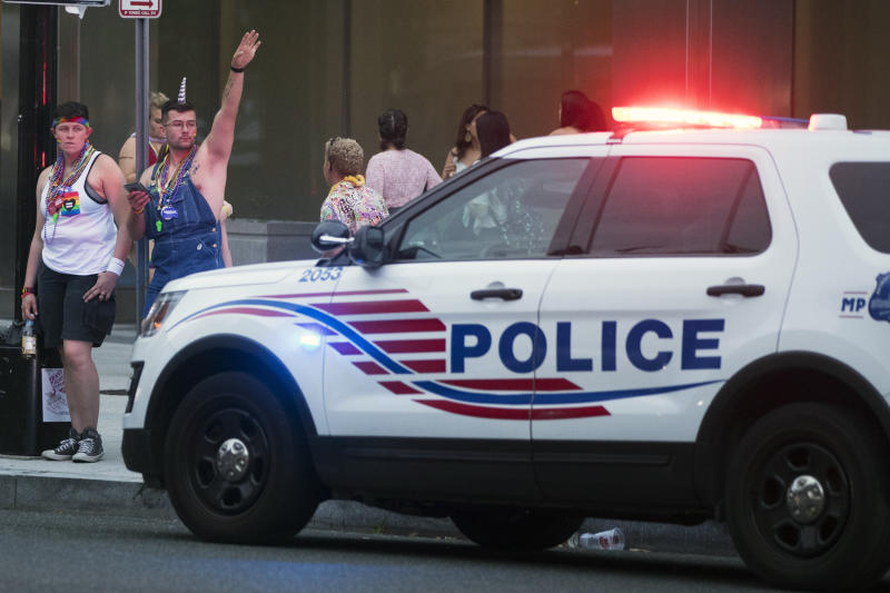 Police keep watch at Dupont Circle at the conclusion of the Capitol Pride Parade in Washington, Saturday, June 8, 2019. Officials in Washington say several people were injured after a panic at the LGBTQ pride parade sent people running through the streets of the nation's capital. (AP Photo/Andrew Harnik)