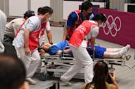 <p>An official is taken away after collapsing during the medal ceremony for the men's 10m air rifle final during the Tokyo 2020 Olympic Games at the Asaka Shooting Range in the Nerima district of Tokyo on July 25, 2021. (Photo by Tauseef MUSTAFA / AFP) </p>