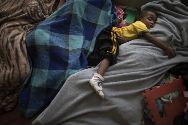 A boy sleeps between his family members as they camp on a footbridge outside the mayor's office in Rio de Janeiro, Brazil, Monday, April 14, 2014. Some of the thousands of people evicted from the abandoned buildings of a telecommunications company on April 11 are camping at the mayor's office, asking for a place to live. (AP Photo/Felipe Dana)