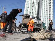Afghan security officials inspect the site of a blast in Kabul, Afghanistan