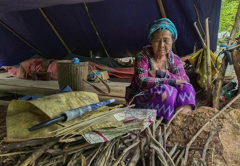 A woman in a blue head wrap and red-and-black plaid top sits near a pile of branches in a makeshift tent
