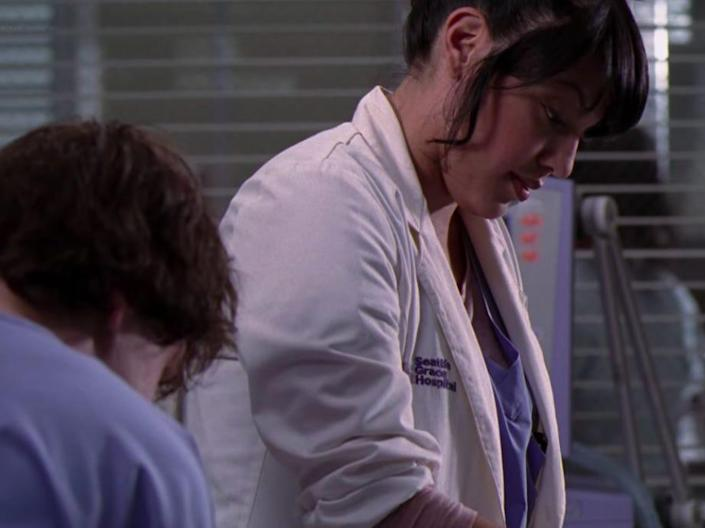 Sara Ramirez as Callie on Greys Anatomy in a hospital room and wearing scrubs and a coat