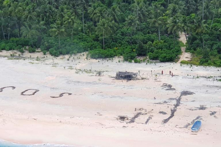The Micronesian sailors were rescued after a search party spotted a giant SOS they had scrawled on the beach
