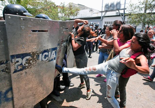 <p>A woman kicks at a riot police shield as relatives of prisoners wait to hear news about their family members imprisoned at a police station where a riot broke out, in Valencia, Venezuela, Wednesday, March 28, 2018. In a state police station housing more than one hundred prisoners, a riot culminated in a fire, requiring authorities to open a hole in a wall to rescue the inmates. (Photo: Juan Carlos Hernandez/AP) </p>
