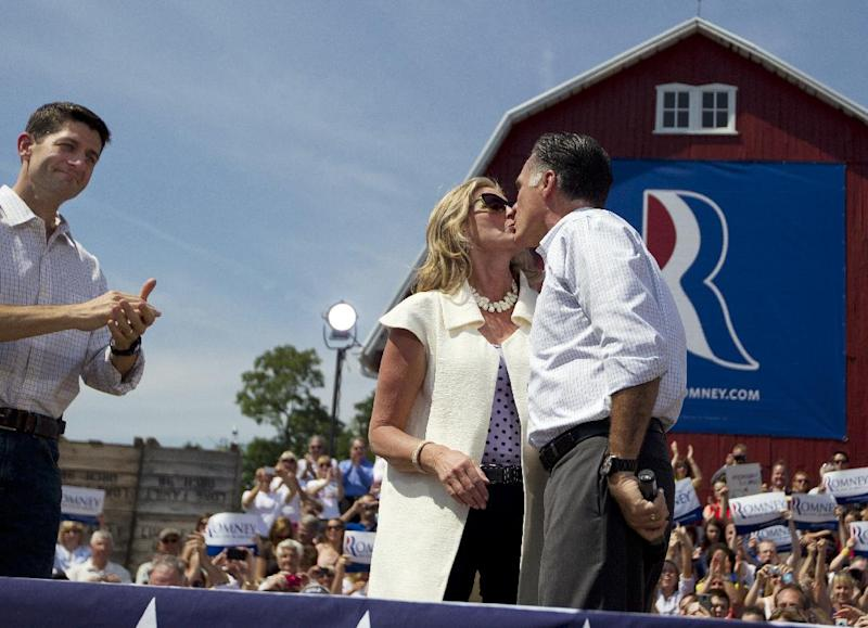 Republican presidential candidate, former Massachusetts Gov. Mitt Romney, right, kisses his wife Ann, as vice presidential running mate Rep. Paul Ryan, R-Wis., looks on during a campaign rally on Friday, Aug. 24, 2012 in Commerce, Mich. (AP Photo/Evan Vucci)