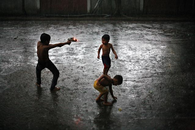 In this Aug. 7, 2013 photo, Rohingya refugee children play in the rain outside their temporary shelter in Medan, Indonesia. Indonesia has been sympathetic to the Rohingya, who have been fleeing violence in Myanmar in greater numbers, and the Indonesian president has sent a letter to his Myanmar counterpart calling for an end to the crisis. But Indonesia has not opened its doors to the Rohingya. It only allows them to stay until they can be resettled elsewhere, which can take years. (AP Photo/Binsar Bakkara)