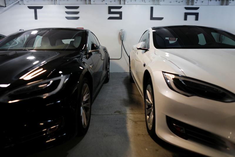 Tesla Model 3s are shown charging in an underground parking lot next to a Tesla store in San Diego,California
