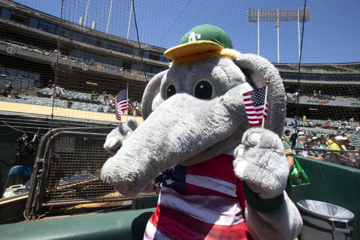 """Oakland Athletics mascot """"Stomper"""" waves a pair of United States flags before a baseball game against the Boston Red Sox, Sunday, July 4, 2021, in Oakland, Calif. (AP Photo/D. Ross Cameron)"""