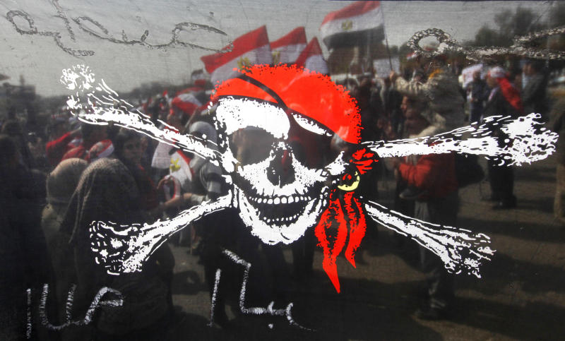 """Egyptian pro-military supporters are seen through a transparent pirate flag criticizing the Muslim Brotherhood during a protest in Cairo, Egypt, Friday, March 1, 2013. Hundreds of pro-military supporters gathered to reject the Muslim Brotherhood and President Mohammed Morsi's rule calling for the military to return to power. Arabic reads """"Egypt's pirates."""" (AP Photo/Amr Nabil)"""