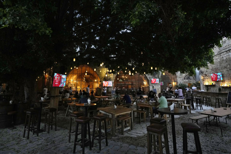 People sit at tables outside a restaurant in Batroun village, north of Beirut, Lebanon, Friday, July 2, 2021. With their dollars trapped in the bank, a lack of functioning credit cards and travel restrictions imposed because of the pandemic, many Lebanese who traditionally vacationed over the summer at regional hotspots are also now turning toward domestic tourism. (AP Photo/Hassan Ammar)