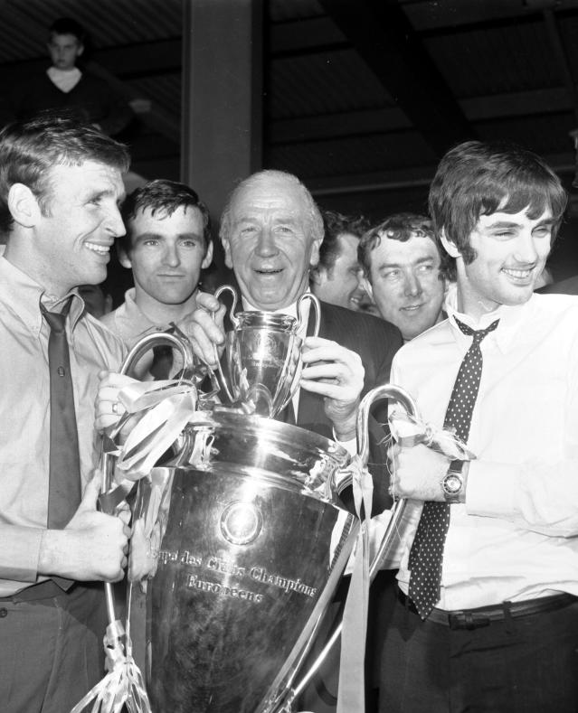 FILE - In this May 30, 1968 file photo, Pat Crerand, left, and George Best, right, of Manchester United hold the European Cup with their manager Matt Busby, at Euston Station, in London, the day after Manchester United beat Portugal's Benfica 4-1 at Wembley, in London. Best is regarded as one of the great players not to win the World Cup. Argentina's Lionel Messi and Portugal's Cristiano Ronaldo are likely to join that list after their teams were eliminated from the 2018 World Cup on Saturday, June 30, 2018 (AP Photo/Victor Boynton, File)