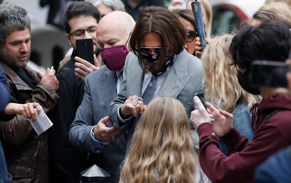 A masked Johnny Depp is surrounded by fans as he arrives for day eight of the trial in his libel suit in London, July 16, 2020.