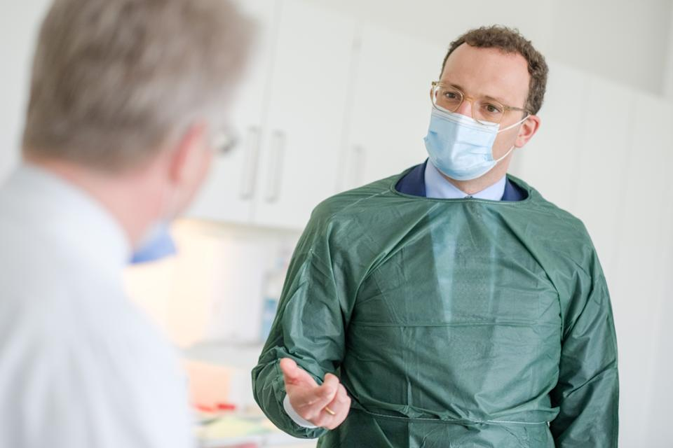 German Health Minister Jens Spahn (R) wears a face mask as he speaks with Christoph Schindler, clinical researcher at the Clinicial Research Center (CRC) of the Medizinische Hochschule Hannover (MHH) medical university, during a visit at the centre's department for research on primary vaccination, on April 28, 2020 in Hanover, northern Germany. (Photo by Ole Spata / POOL / AFP) (Photo by OLE SPATA/POOL/AFP via Getty Images)