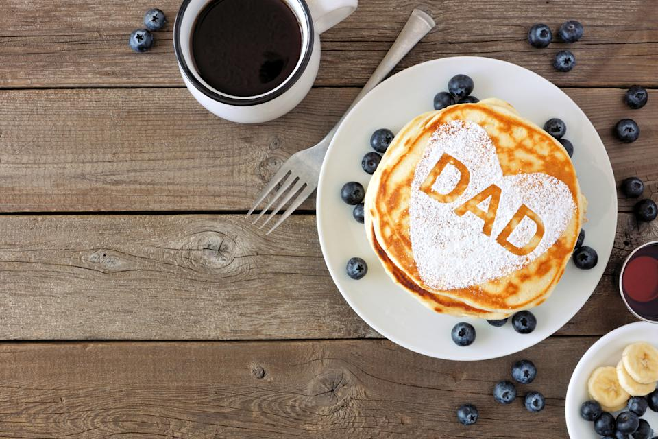 Pancakes with heart shape and DAD letters. Fathers Day breakfast concept. Above view corner border on a rustic wood background.