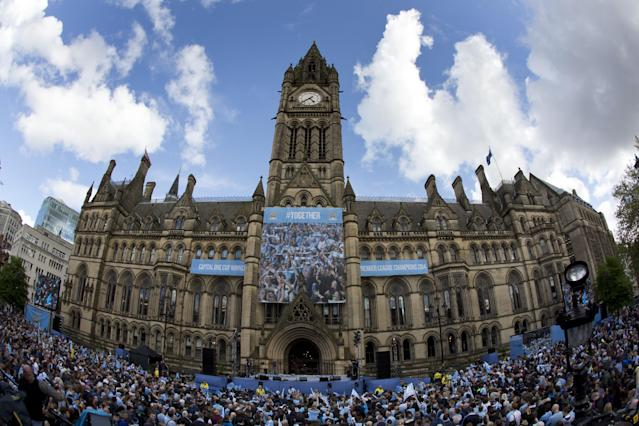 Crowds gather outside of Manchester's Town Hall as Manchester City supporters prepare to celebrate with a parade in the city centre the day after their team won the English Premier League soccer title in Manchester, England, Monday May 12, 2014. (AP Photo/Jon Super)