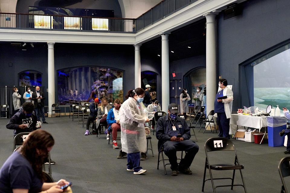 People sit in the observation area after receiving a dose of the Moderna Covid-19 vaccine at the American Museum of Natural History vaccination site in New York, U.S., on Friday, April 30, 2021. (Gabby Jones/Bloomberg via Getty Images)