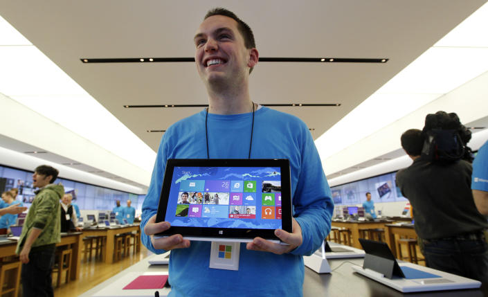 FILE - In this Friday, Oct. 26, 2012, file photo, Microsoft store product advisor Stuart Pitts displays the new Surface tablet computer as customers enter the store as it opened in Seattle. The Surface is Microsoft's first attempt at a general-purpose computer. In the past, it made the software and left it to other companies to make the machines. But to catch the tablet wave led by Apple's iPad, Microsoft felt it needed to make its own device. (AP Photo/Elaine Thompson, File)