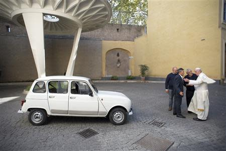 Pope Francis (R) is presented with a Renault 4 car during a private audience with Don Renzo Zocca at the Vatican in this picture taken September 7, 2013 and released by Osservatore Romano September 10, 2013. REUTERS/Osservatore Romano