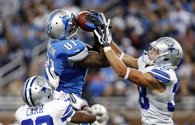 Detroit Lions wide receiver Calvin Johnson (81) pulls in a 54-yard reception as Dallas Cowboys cornerback Brandon Carr (39) and Dallas Cowboys defensive back Jeff Heath (38) defends in the fourth quarter of an NFL football game in Detroit, Sunday, Oct. 27, 2013. (AP Photo/Duane Burleson)