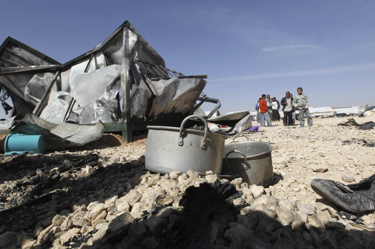 Syrian refugees stand near their damaged belongings, a result of a clash between security forces and the refugees at the Al-Zaatri refugee camp in the Jordanian city of Mafraq, near the border with Syria, April 6, 2014. At least one Syrian refugee was killed in Jordan's sprawling Zaatari camp when hundreds of refugees clashed with security forces, residents said on Saturday. They said scores of refugees in the sprawling camp close to the Syrian border were injured as baton-wielding anti-riot police used tear gas to disperse stone-throwing refugees who set fire to official offices and caravans. REUTERS/Muhammad Hamed (JORDAN - Tags: POLITICS CIVIL UNREST TPX IMAGES OF THE DAY)