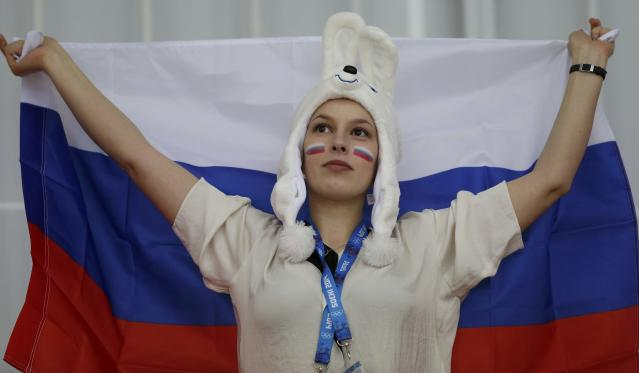 A Russian supporter holds up her national flag before the women's 3,000 metres speed skating race at the Adler Arena during the 2014 Sochi Winter Olympics February 9, 2014. REUTERS/Issei Kato (RUSSIA - Tags: OLYMPICS SPORT SPEED SKATING)