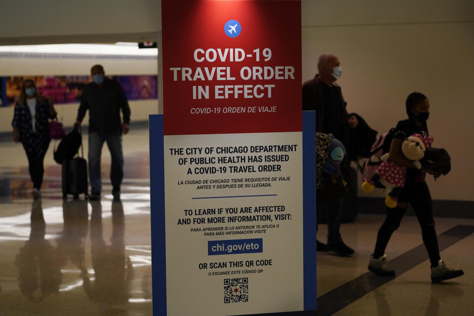 FILE - In this Nov. 24, 2020, file photo, air travelers arriving at Midway Airport in Chicago are reminded of the city's COVID-19 travel orders. Data from roadways and airports shows millions could not resist the urge to gather on Thanksgiving, even during a pandemic. (AP Photo/Charles Rex Arbogast, File)