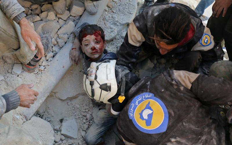 Syrian civil defence volunteers, known as the White Helmets, rescue a boy from the rubble following a reported barrel bomb attack on the Bab al-Nairab neighbourhood of Aleppo - AFP