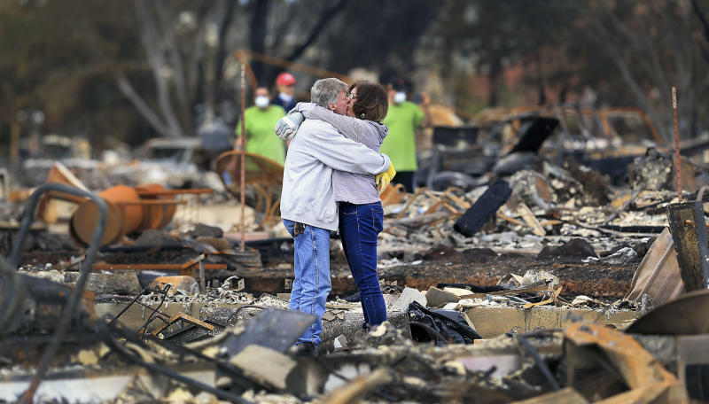 FILE- In this Oct. 20, 2017, file photo Gordon Easter and finance Gail Hale embrace as they return to their home on Hopper Lane in Coffey Park, in Santa Rosa, Calif. .  As California counties face the prospect of increased utility power shut-off meant to prevent wildfires, counties with more resources are adapting much more easily to the challenge than poorer ones. (Kent Porter/The Press Democrat via AP, File)