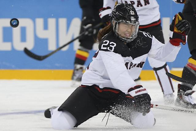 Ami Nakamura of Japan lands on her knees as the puck get away form her during the game against Germany at the 2014 Winter Olympics women's ice hockey tournament at Shayba Arena, Thursday, Feb. 13, 2014, in Sochi, Russia. (AP Photo/Petr David Josek)