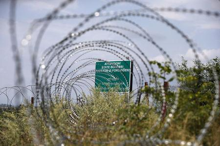 FILE PHOTO: A warning sign behind a wire barricade erected by Russian and Ossetian troops along Georgia's de-facto border with its breakaway region of South Ossetia in the village of Khurvaleti, Georgia, July 14, 2015. REUTERS/David Mdzinarishvili/File Photo