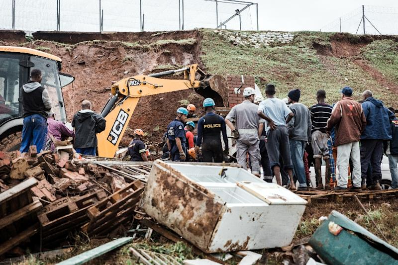 Police officers try to rescue people trapped in their homes destroyed in a mudslide following torrential downpours and flash floods, near Westcliff Secondary School in Chatsworth, south of Durban (AFP Photo/RAJESH JANTILAL)