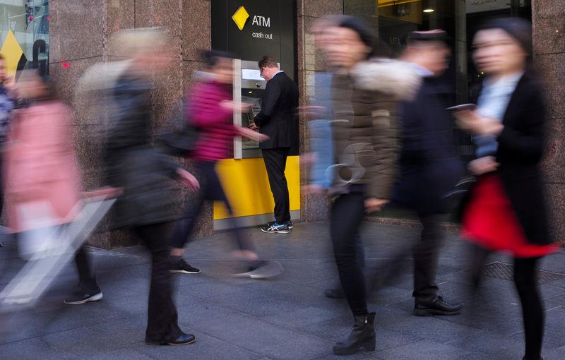 FILE PHOTO: A man banks at a Commonwealth Bank automatic teller machine in Sydney, Australia