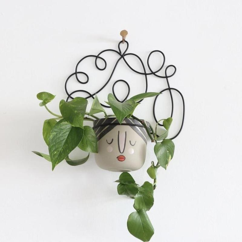 """<p><strong>The Holistic Habitat </strong></p><p>holistichabitatclt.com</p><p><strong>$50.00</strong></p><p><a href=""""https://holistichabitatclt.com/collections/all/products/rosa-hanging-pot"""" rel=""""nofollow noopener"""" target=""""_blank"""" data-ylk=""""slk:Shop Now"""" class=""""link rapid-noclick-resp"""">Shop Now</a></p><p>Why go basic when you can have this pretty plant lady snoozing on your wall? It's your wall planter, but I think you should def. name her. Looks like a """"Betty"""" to me. Up to you though! </p>"""