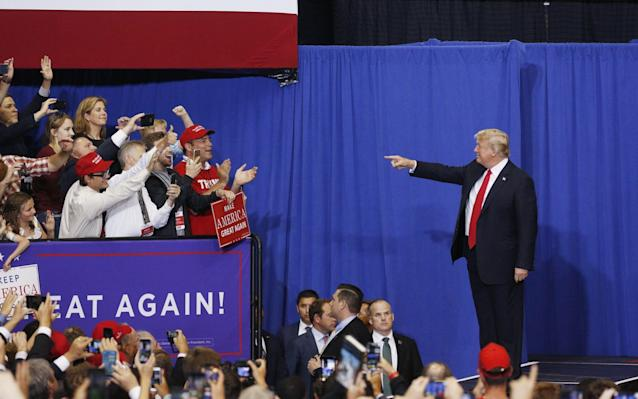 "Donald Trump returned to the campaign trail on Tuesday night with a familiar refrain, criticising Mexico for failing to stop the flow of illegal immigrants to the US and promising to make Mexico pay for his proposed border wall. And the result was the same: Enthusiastic cheers from supporters in Nashville, Tennessee, followed by a swift promise from the Mexican president that no such thing would ever happen. Mr Trump took his message out on the road as part of efforts to shore up Republican votes during what could be tricky mid-term elections in November. Democrats hope an unpopular president could help them wrest back control of the Senate and the House of Representatives. Donald Trump gestures to attendees as he arrives onstage at a rally in Nashville, Tennessee Credit: Luke Sharrett/Bloomberg But Mr Trump returned to the talking points that gave him a shock win in 2016. ""I don't want to cause a problem, but in the end, Mexico's gonna pay for the wall ,"" he said to roars of approval. ""They do absolutely nothing to stop people from going through Mexico, from Honduras and all these other countries... They do nothing to help us."" Mexico has repeatedly said it has no obligation to help the US build a wall, and Mr Trump has in the past backed away from the pledge only to return to it. Again on Tuesday Enrique Pena Nieto, the Mexican President, insisted that his country would never pay for its construction. President @realDonaldTrump: NO. Mexico will NEVER pay for a wall. Not now, not ever. Sincerely, Mexico (all of us).— Enrique Peña Nieto (@EPN) May 30, 2018 Otherwise, Mr Trump used the rally to fire up his base by celebrating his achievements in office, from a slew of positive economic indicators to making good on his promise to move the US embassy in Israel to Jerusalem. He appealed for Republican unity and said the elections need not mean the party that holds the White House loses congressional seats. ""In November, we will reverse a trend,"" he said. At a glance 