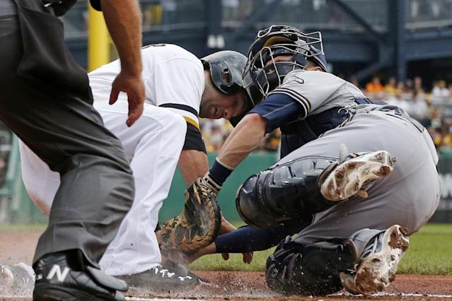Pittsburgh Pirates' Neil Walker, center, is tagged out by Milwaukee Brewers catcher Jonathan Lucroy during the second inning of a baseball game in Pittsburgh Sunday, June 8, 2014. Walker was attempting to score from third on a single to right field by Pirate's Gaby Sanchez. (AP Photo/Gene J. Puskar)