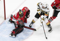 Vegas Golden Knights' William Carrier (28) is stopped by Chicago Blackhawks goalie Corey Crawford (50) who saves the puck with his helmet during first-period NHL Western Conference Stanley Cup playoff hockey action in Edmonton, Alberta, Sunday, Aug. 16, 2020. (Jason Franson/The Canadian Press via AP)