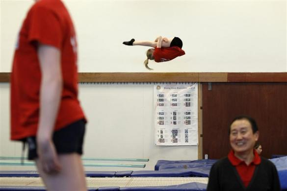Crystal Palace diving club member Lexie Howard (C) practices during a training session in a dry diving gym in London March 9, 2012.