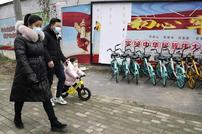 Residents walk past a row of bicycles in Wuhan.