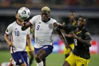 United States forward Gyasi Zardes (9) and Jamaica's Oniel Fisher (8) chase after a loose ball in the second half of a CONCACAF Gold Cup quarterfinals soccer match, Sunday, July 25, 2021, in Arlington, Texas. (AP Photo/Brandon Wade)
