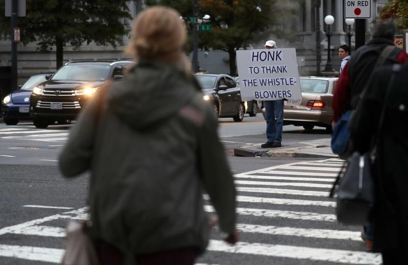 A person holds a sign supporting whistleblowers outside of the White House, in Washington