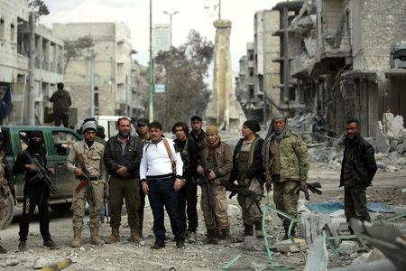 Rebel fighters pose for a picture in a damaged neighbourhood in the northern Syrian town of al-Bab