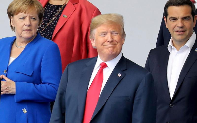 Angela Merkel and Donald Trump pose for a family photo ahead of the NATO opening ceremony - POOL AFP