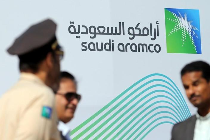 Logo of Aramco is seen as security personnel stand before the start of a press conference by Aramco at the Plaza Conference Center in Dhahran