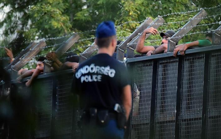 Hungarian police officers stand guard in front of a metal gate at the closed M5 highway to block migrants, at the Hungarian-Serbian border near Roszke station on September 15, 2015 (AFP Photo/Attila Kisbenedek)