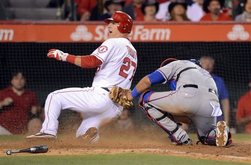 Los Angeles Angels' Mike Trout, left, slides in under the tag of Texas Rangers catcher Yorvit Torrealba on a sacrifice fly by Kendrys Morales during the seventh inning of their baseball game, Saturday, June 2, 2012, in Anaheim, Calif. (AP Photo/Mark J. Terrill)