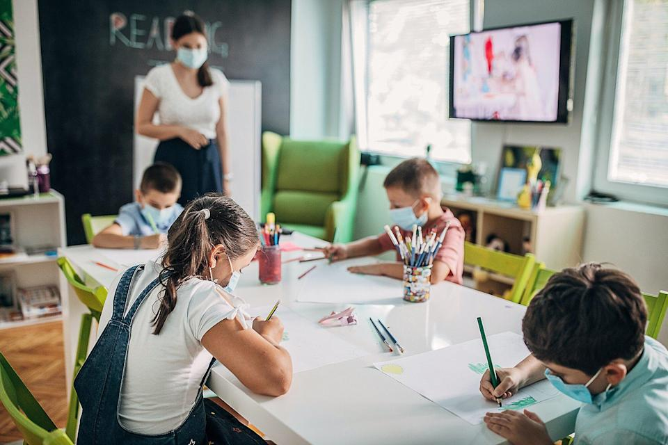 Children with protective face masks drawing