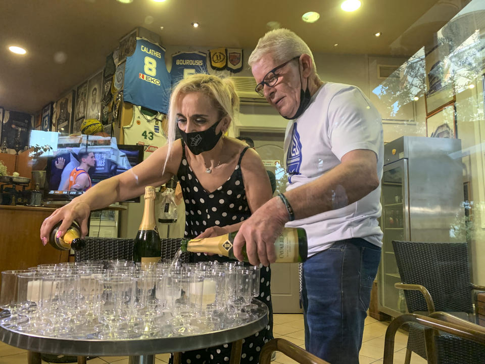 Coffee shop owner Yiannis Tzikas and his wife Kaiti Drimba pour champagne into plastic glasses after the Milwaukee Bucks win the NBA title, in the Sepolia district of Athens on Wednesday, July 21, 2021. Milwaukee Bucks star Giannis Antetokounmpo grew up in Sepolia and used to stop at the coffee shop before basketball practice as a teenager. (AP Photo/Derek Gatopoulos)