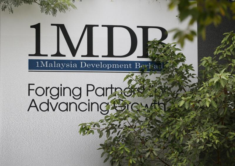 Foliage partly covers a 1Malaysia Development Berhad (1MDB) billboard at the funds flagship Tun Razak Exchange development in Kuala Lumpur, July 3, 2015. — Reuters pic